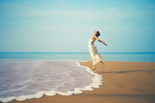 Young lady in white dress jumping on the beach